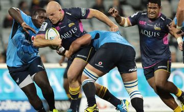 Stephen Moore of the Brumbies is tackled by the Bulls