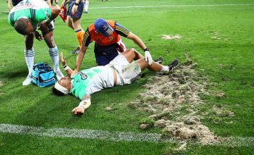 Ash Dixon lies injured next to the ripped up AAMI Park turf